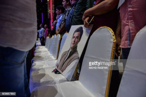 A portrait of President for the Indian National Congress party Rahul Gandhi is seen on a chair as people stand for the national anthem of India...