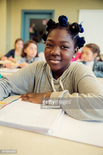 Portrait of preteen African-American girl in classroom, sitting at her desk.