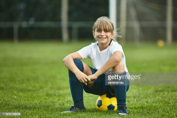 portrait of pre-teen female footballer sitting on ball - sports training camp stock pictures, royalty-free photos & images