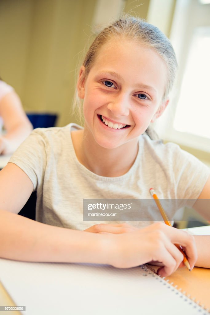 Portrait of preteen girl in classroom, sitting at her desk. : Stock Photo