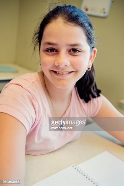 """portrait of preteen girl in classroom, sitting at her desk. - """"martine doucet"""" or martinedoucet stock pictures, royalty-free photos & images"""