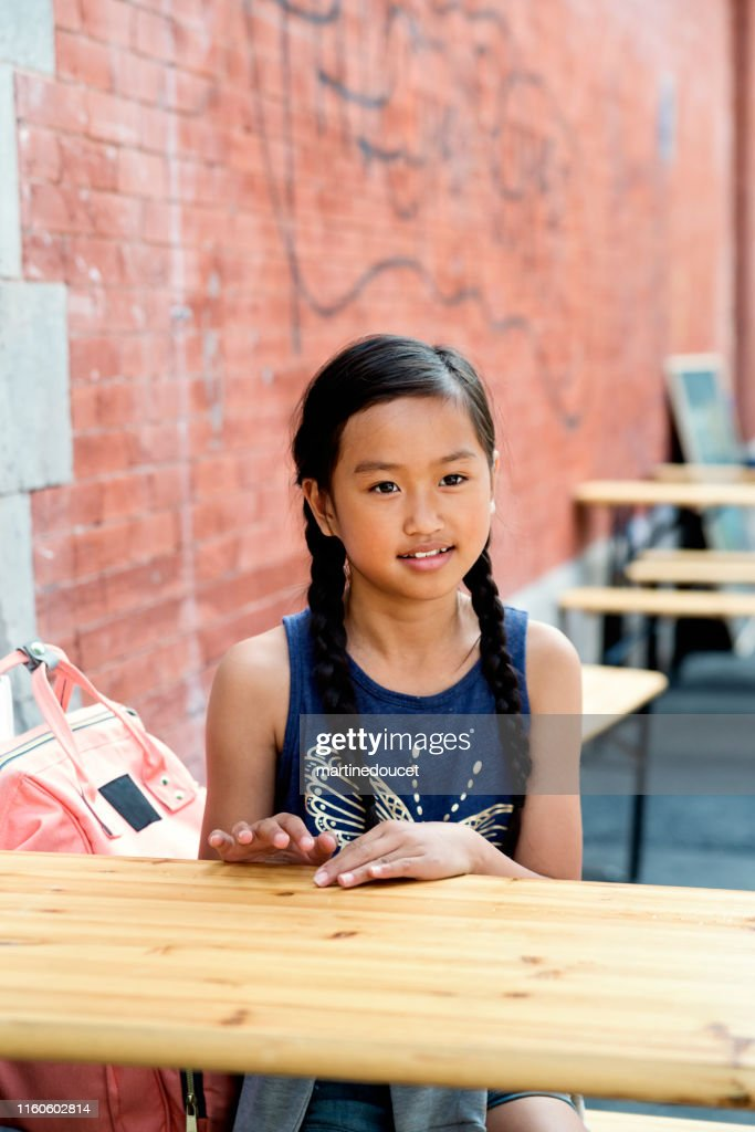 Portrait of preteen girl sitting at a city terrace. : Stock Photo