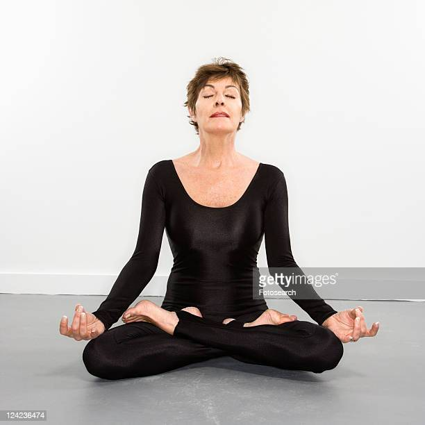 portrait of pretty caucasian woman in spandex bodysuit sitting in meditation lotus pose. - women wearing spandex stock photos and pictures