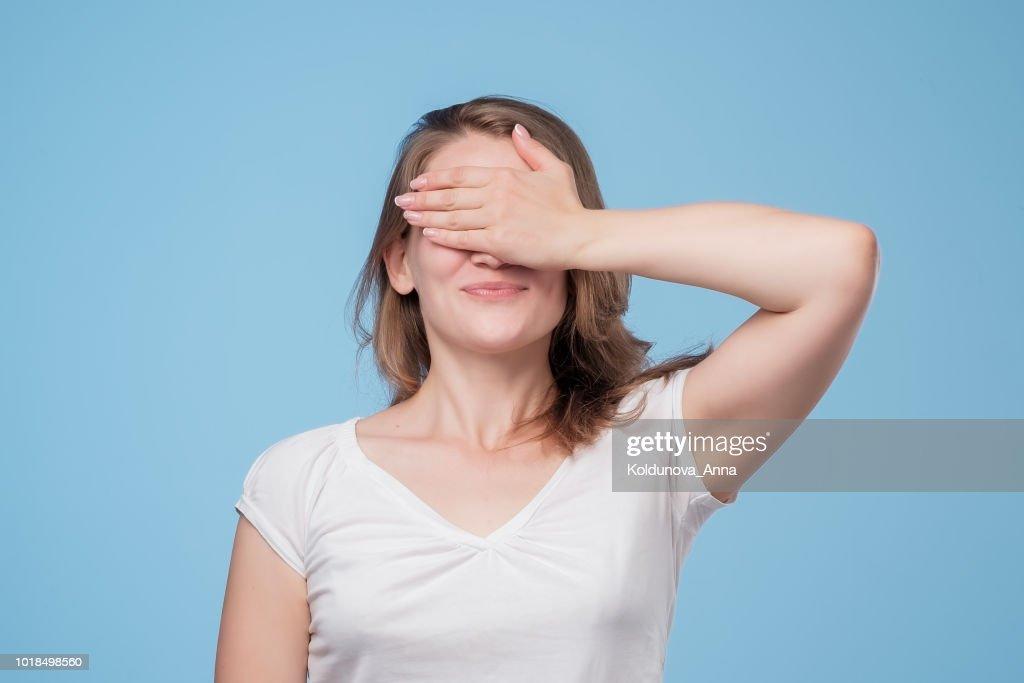 Porträt von ziemlich kaukasischen Frau mit langen Haaren lachen ihre Augen mit der Hand bedecken. : Stock-Foto
