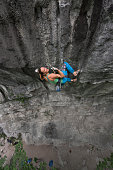 Portrait of pretty female rock climber hanging on craggy rock