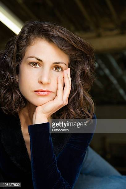 Portrait of pretty mid adult Caucasian woman with head on hand making eye contact.