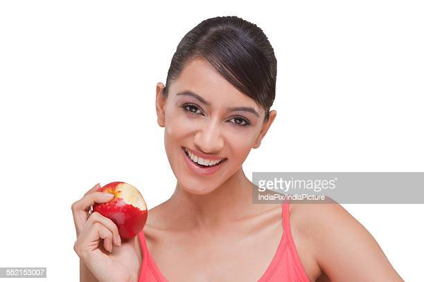 Portrait of pretty woman with bitten apple over white background