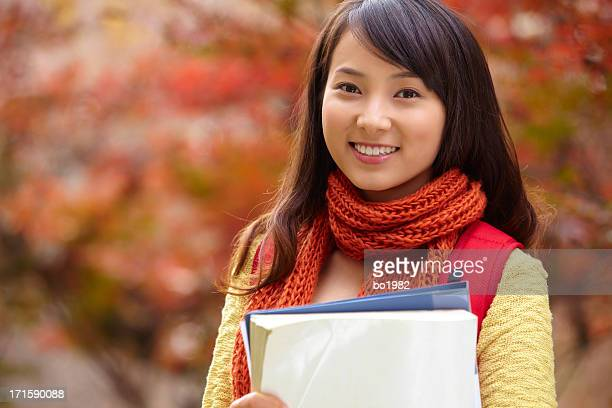 portrait of pretty young college student in autumn campus