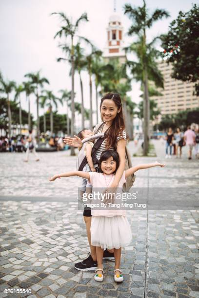 Portrait of pretty young mom with her children smiling at the camera joyfully in front of the Hong Kong Clock Tower.
