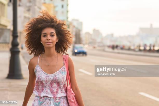 Portrait of pretty young woman walking on Malecon, Havana at dusk