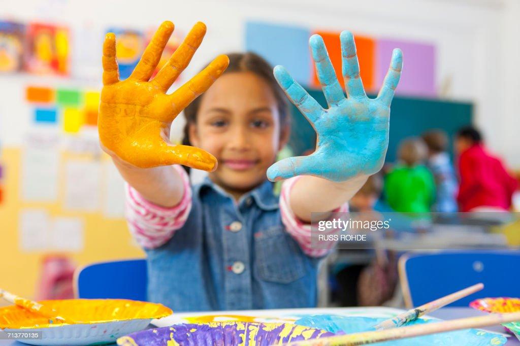 portrait of primary schoolgirl with painted hands in classroom