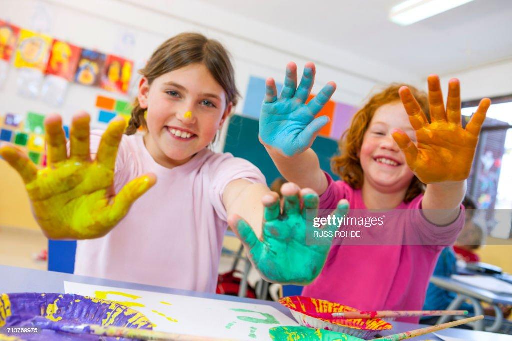 portrait of primary schoolgirls with painted hands in classroom
