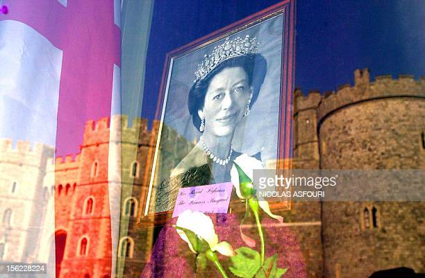 A portrait of Princess Margaret stands in a gift shop with the reflection of Windsor Castle 15 February 2002 where her private funeral ceremony will...
