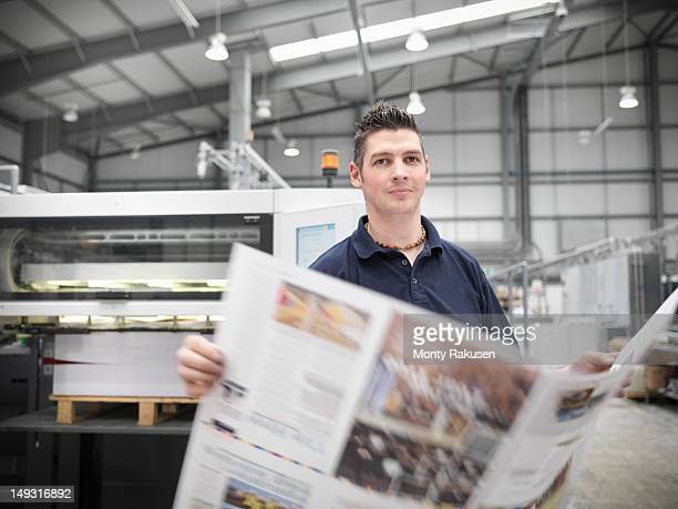 Portrait of printworker holding pages from printing press