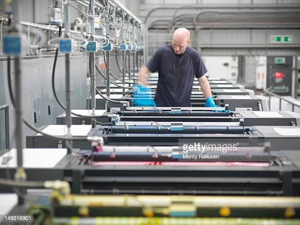 portrait of printworker loading ink into press in printworks - printing press stock pictures, royalty-free photos & images