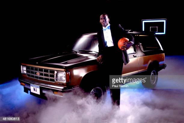 Portrait of professional basketball player Michael Jordan of the Chicago Bulls dressed in a tuxedo with a basketball under one arm as he poses with...