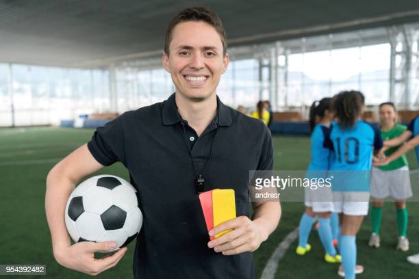 portrait of professional referee holding the yellow and red cards and soccer ball looking at camera smiling - female umpire stock pictures, royalty-free photos & images
