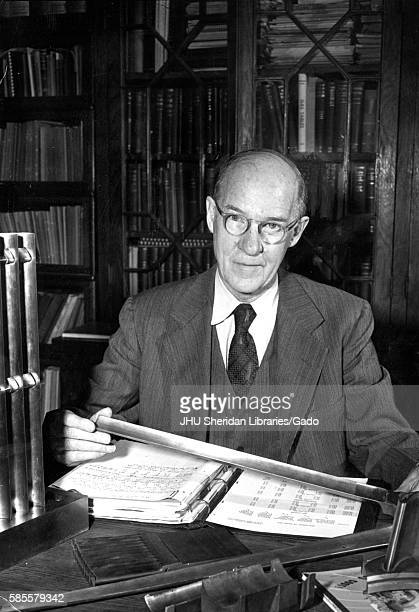 A portrait of Professor of engineer at Whiting School of Engineering Alexander Graham Christie in his office in front of a binder full of papers at...