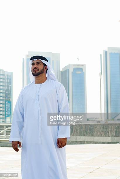 Portrait of proud man in Middle Eastern traditional dress, Dubai cityscape in background, UAE