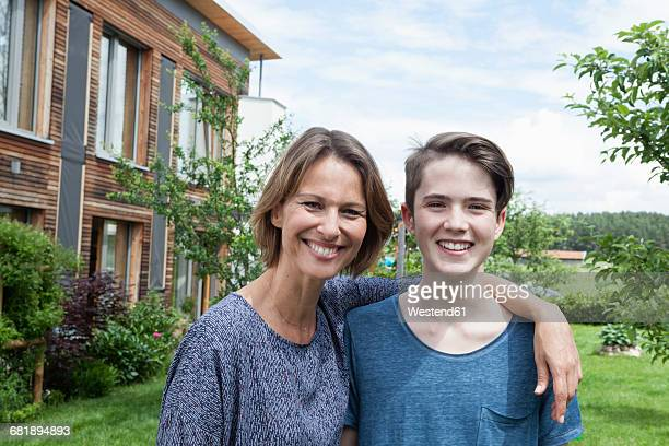 Portrait of proud mother with son in garden
