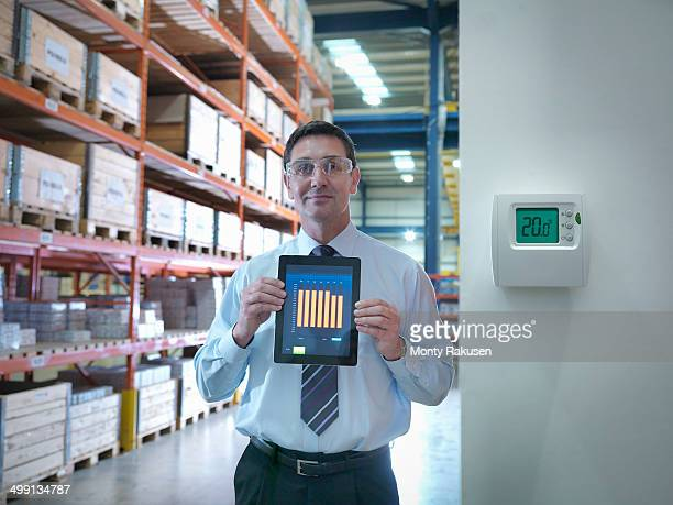 Portrait of proud office worker showing energy saving on digital tablet in factory