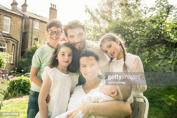 Portrait of proud parents with four beautiful children in sunlit garden