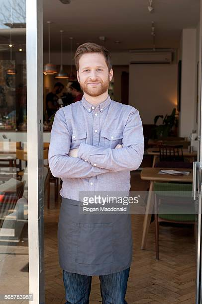 Portrait of proud young male cafe owner in doorway