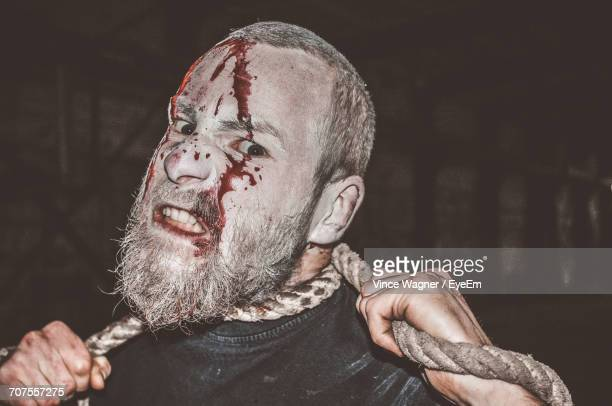Portrait Of Psychopath Covered In Blood Strangling Himself At Night