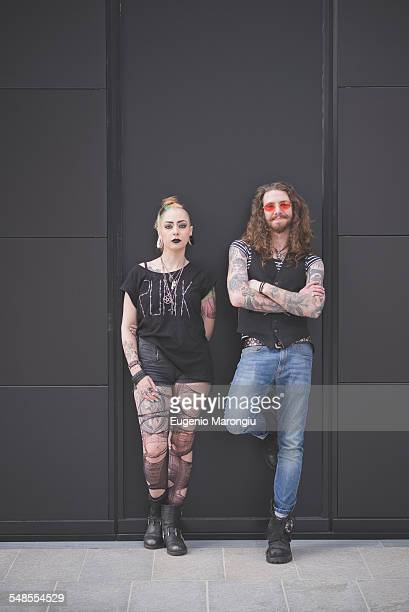 portrait of punk hippy couple leaning against wall - hippie woman stock photos and pictures