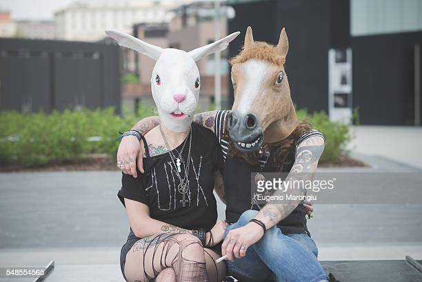 portrait of punk hippy couple wearing rabbit and horse costume masks - freaky couples stock photos and pictures