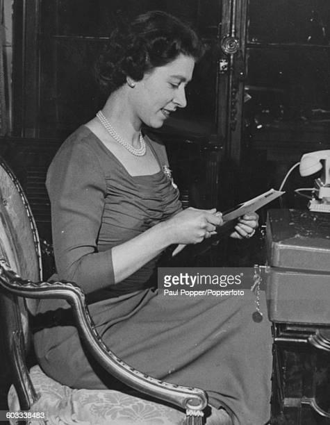 Portrait of Queen Elizabeth II opening letters at her desk in Buckingham Palace London January 1959