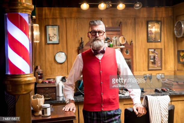 Portrait of quirky senior man in traditional old english barber shop