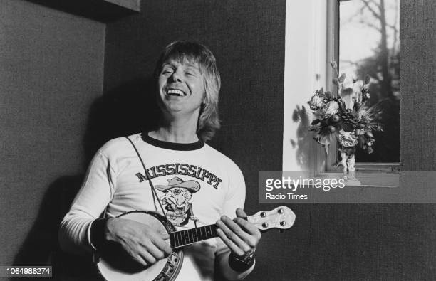 Portrait of radio disc jockey Joe Brown playing a banjolele photographed for Radio Times in connection with the George Formby anniversary television...