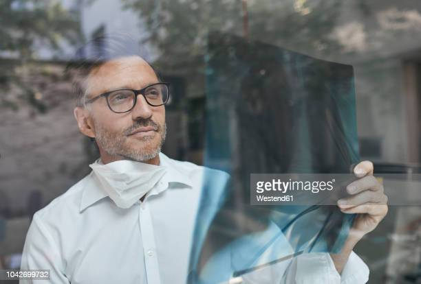 portrait of radiologist behind windowpane looking at x-ray image - medical x ray stock pictures, royalty-free photos & images