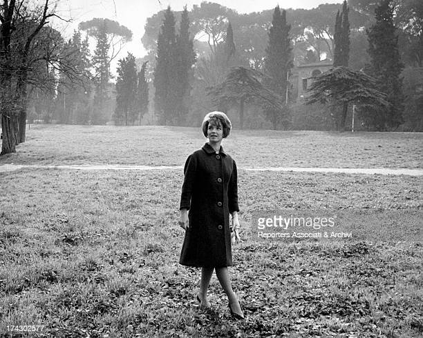 Portrait of RAI announcer and presenter Aba Cercato who makes as if to walk on the grass in a foggy and hazy atmosphere December 1961