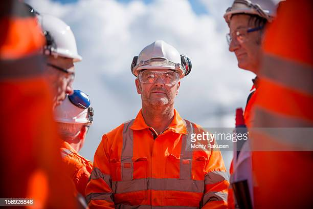 Portrait of railway worker with colleagues wearing protective clothing