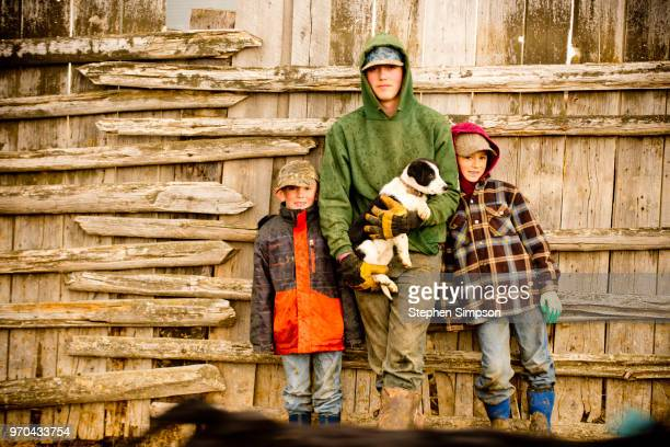 portrait of ranch family with border collie puppy on montana ranch - livestock branding stock photos and pictures