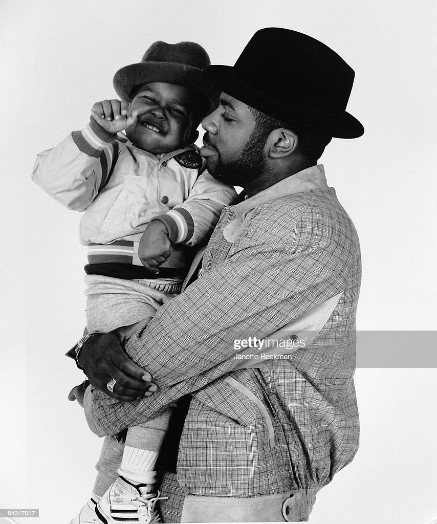 Portrait of rapper Jam Master Jay (or Jason William Mizell, 1965 - 2002) holding his son, 1991. New York.