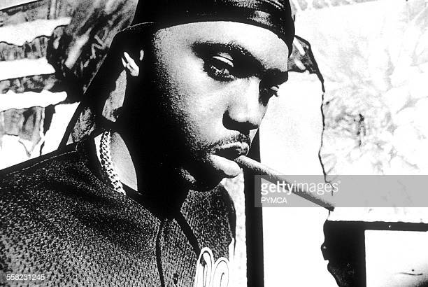 portrait of Rapper Nas with a black bandana and a neck chain holding a cigar in his mouth