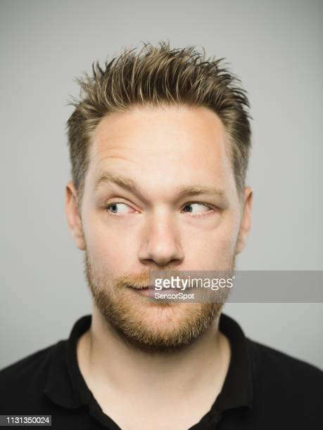 portrait of real caucasian man with blank expression looking to the side - suspicion stock pictures, royalty-free photos & images