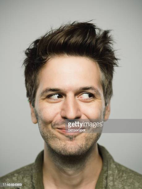 portrait of real caucasian man with happy expression looking to the side - smirking stock pictures, royalty-free photos & images
