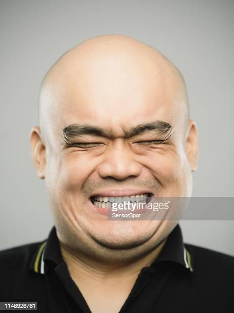 portrait of real chinese adult man with extreme expression and eyes closed - clenching teeth stock pictures, royalty-free photos & images