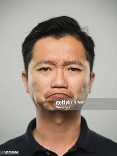 portrait of real chinese man with disappointed expression - sneering stock pictures, royalty-free photos & images
