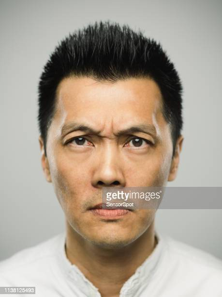 portrait of real chinese man with worried expression - frowning stock pictures, royalty-free photos & images