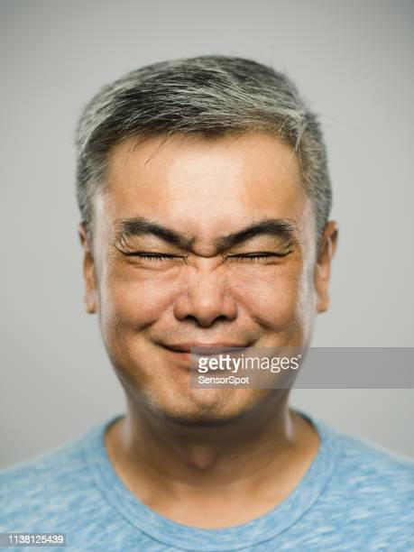 portrait of real chinese mature man with disgusted expression and eyes closed - grimacing stock pictures, royalty-free photos & images