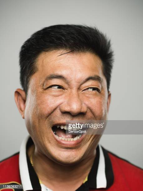 portrait of real chinese mature man with ecstatic expression looking to the side - hysteria stock pictures, royalty-free photos & images