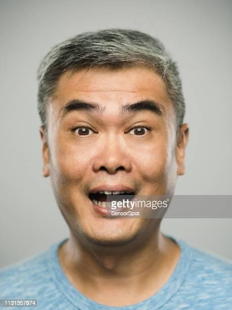 portret van de echte chinese volwassen man met een verbaasde uitdrukking te kijken naar camera - real people stockfoto's en -beelden