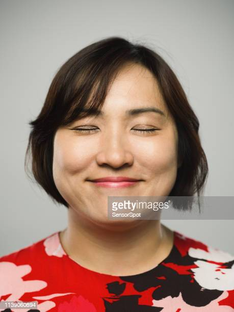 portrait of real chinese mature woman with happy expression and eyes closed - serene people stock pictures, royalty-free photos & images
