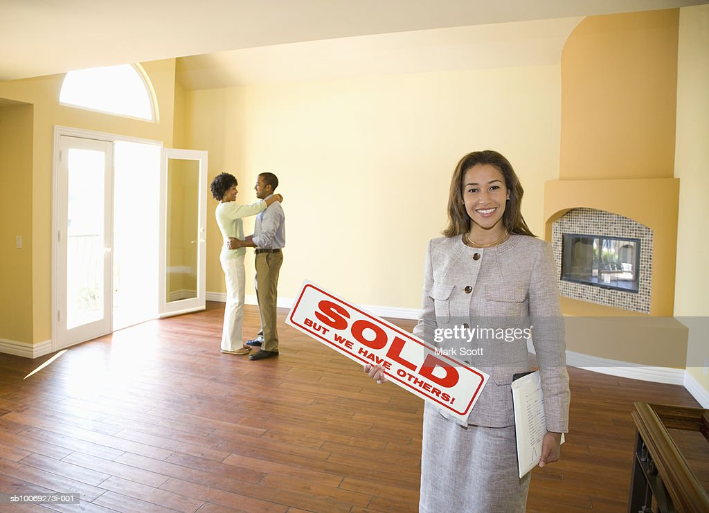 Portrait of real estate agent with couple in background in new home : Stockfoto