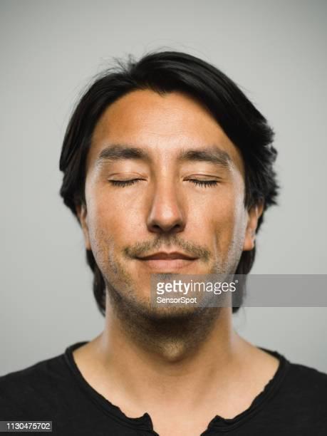 porträt von echten hispanic mann mit leeren ausdruck und geschlossenen augen - augen geschlossen stock-fotos und bilder
